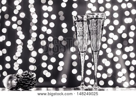 Two Glasses Of Champagne With Christmas Toys. Festive Lights Bokeh Background