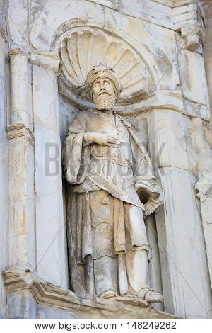 COIMBRA PORTUGAL - AUGUST 1 2016: Sculpture of a Saint with a turban on the facade of the Old Cathedral or Se Velha Coimbra Portugal