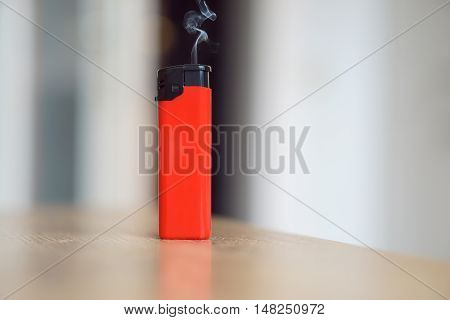 Red lighter with smoke coming out of it