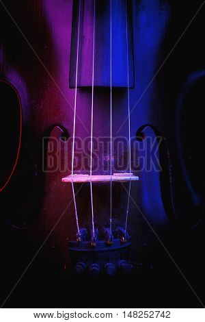 Old Violin Illuminated In Blue And Purple
