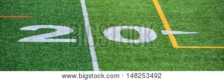 The 20-yard-line of an american football field with artificial turf
