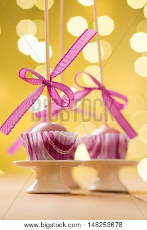 Pink Christmas cake pops sticking upside down in miniature cupcake liners. Very shallow depth of field with Christmas lights in the background