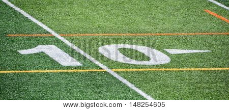 The 10-yard-line of an american football field with artificial turf