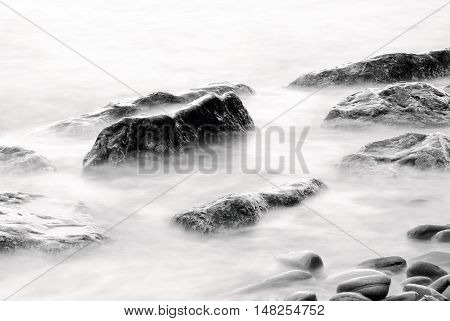 cool rocks isolated into the water of the sea