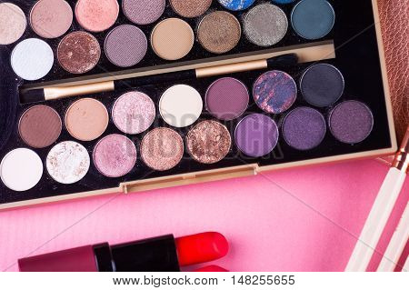 Face makeup brushes eye shadows color palette and red lipstick on pink and brown background.