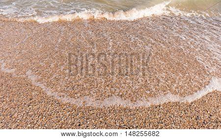 soft clean waves with foam on sandy seashore