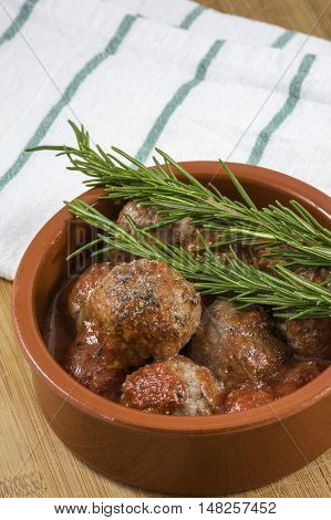 Tasty croquettes in clay bowl with rosemary on kitchen towel