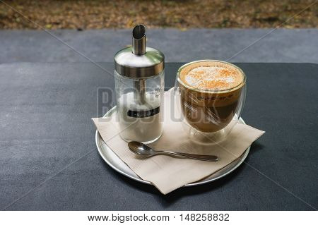 hot fresh coffee in see through glass with sugar in jar silver spoon on black table at coffee time / hot fresh coffee