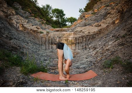 man in blue shirt doing second step of surya namaskar, uttanasana forward bending pose outdoor
