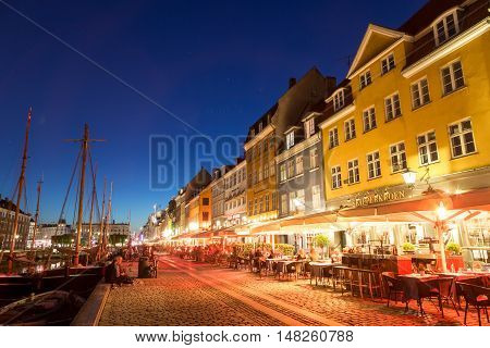 Copenhagen, Denmark - May 08, 2016: Famous Nyhavn harbor with people in bars and cafes on a summer night