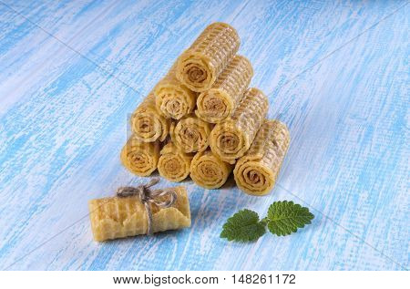 Wafer rolls on a wooden blue background. Wafer rolls are folded hpyramid.