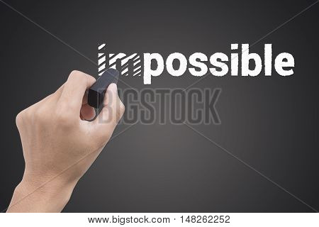 hand holding black eraser changing the word impossible to possible concept business possible