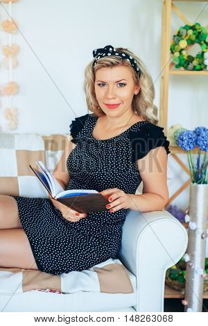 Young gorgeous blonde reading a book in the room. The concept of lifestyle.