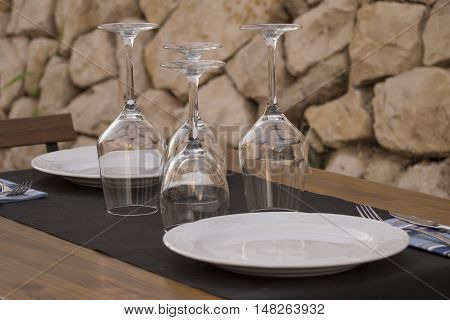 Table with white dishes and wine glasses upside down with stone background