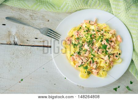Italian Wholemeal Pasta Tagliatelle with Salmon and Parsley. Fresh pasta with smoked salmon in the sauce on white wooden background with place for text. Italian cuisine concept. Copy space. Top view.