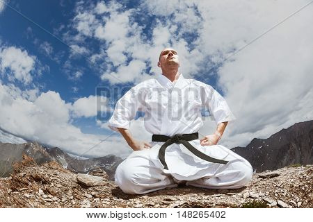 Man in kimono sits in yoga relax pose on the top of mountain