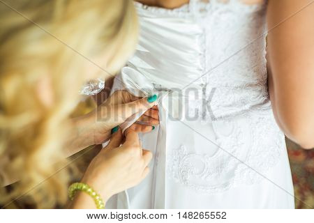 Bridesmaid Helping The Bride With The Wedding Dress