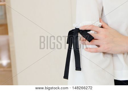 Woman hand on long white sleeve with black string bow tie style details. Close up trendy fashion.