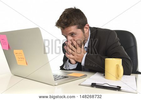 young attractive businessman looking worried face expression suffering stress at office laptop computer having work problem sitting on desk with paperwork isolated on white background