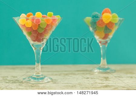 Two glass jar full of jellybeans on wooden table with blue background