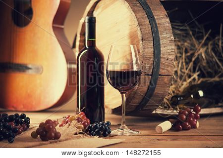 Wine bottle, glass, grapes, barrel and guitar