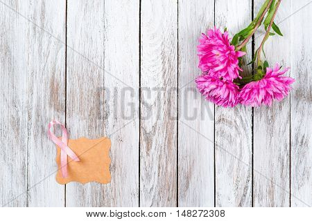 Pink breast cancer ribbon and pink flowers on the wooden background.