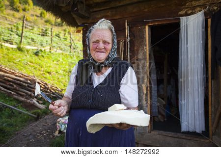 Salciua, Romania - September 14, 2016: Old rural woman selling cheese at the farm in the mountains