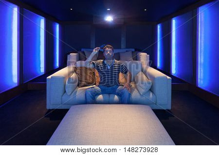 Man watching a movie in the home theater, luxury interior