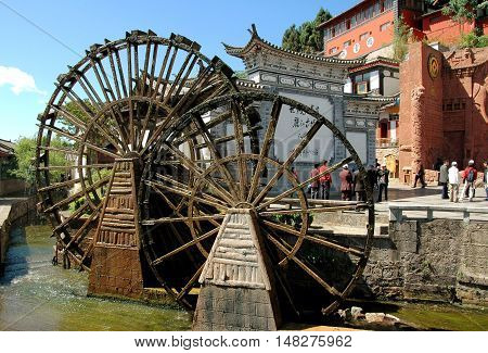 Lijiang China - April 19 2006: Two traditional Chinese wooden water wheels built on a stream flowing through Si Feng Square