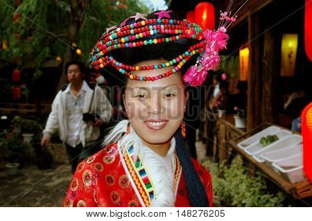 Lijang China - April 21 2006: Chinese woman dressed in traditional Naxi clothing with a beaded headdress at a restaurant on Xing Hua Street