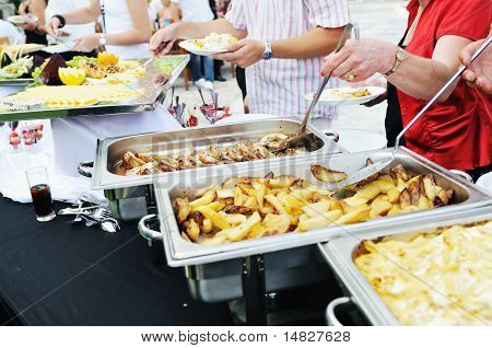 people choosing food from table on catering and buffet party on business seminar conference or wedding