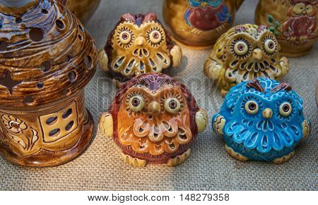 Owls - pottery handmade from clay glazed in natural sunlight against a background of other ceramic products. Image focus on brown owl