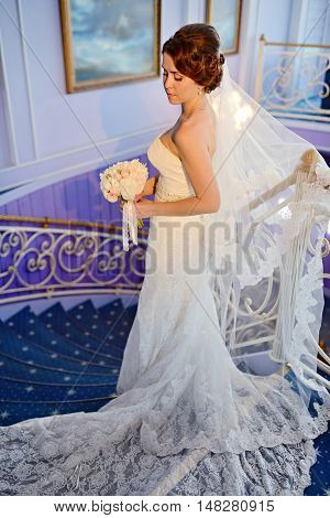 Beauty Bride In Bridal Gown With Bouquet And Lace Veil Indoors. Beautiful Model Girl In A White Wedd