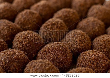 Dark colored sweets. Rows of brown candies. Delicious dessert from russian cuisine. Butter and crumbled cookies.