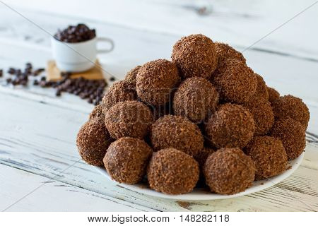 Brown candies on white plate. Pile of dark sweets. Homemade chocolate balls. Butter mixed with crumbled cookies.