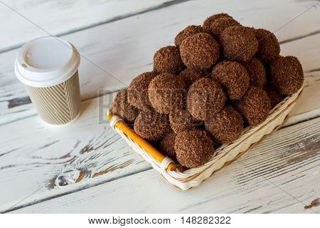 Sweets in wicker basket. Hot drink cup near desserts. Rum balls and espresso. Sweet food on white table.