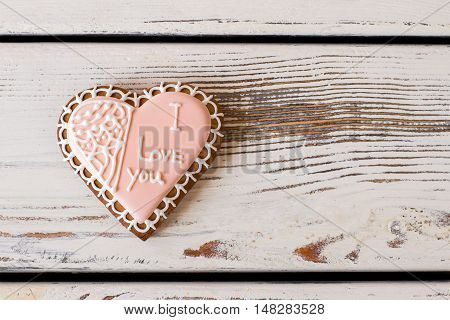 Heart cookie with inscription. Pink frosted biscuit. The most important message. Convey the warmth of heart.
