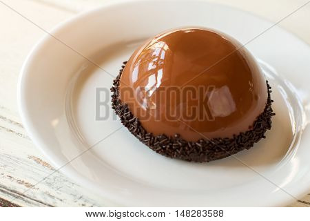 Brown half sphere cake. Dessert with smooth surface. Chocolate mousse and mirror glaze. Tasty sweet dish in cafeteria.