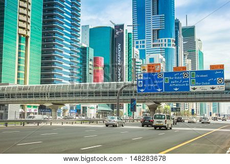Dubai, United Arab Emirates - May 1, 2013: Dubai Financial Centre Metro station and footbridge. Underground lines without a driver in the Dubai metro. Traffic on Sheikh Zayed Road, the highway E 11.