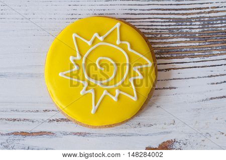 Top view of decorated cookie. Biscuit with bright icing. You can touch the star. Crispy dessert on white table.