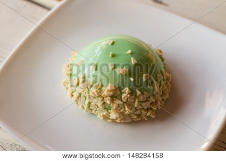 Sweet dish with green icing. Glazed dome cake on plate. Delicacy with mint mousse. Plain design of confectionery.