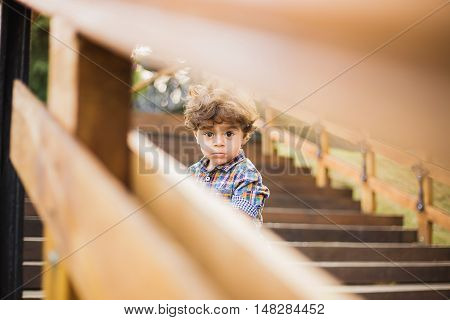 Portrait Of Cute Child Sitting On Wood Stairs