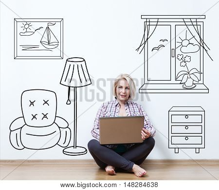 Smiling beautiful middle aged woman sitting on floor with laptop, considering new idea.