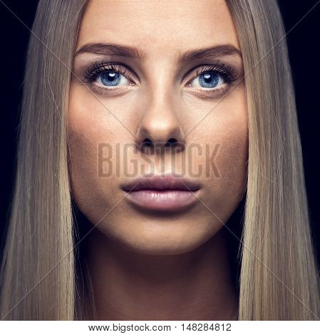 Closeup portrait of beautiful young woman with blond hair over black background