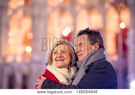 Senior couple in winter clothes on a walk in illuminated night city, hugging. Historical building. Vienna, Austria.