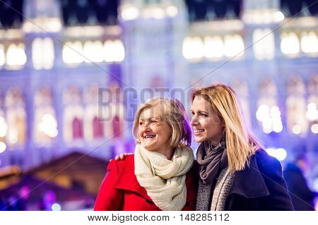 Two beautiful women, mother and daughter in winter clothes on a walk in illuminated night city. Historical building. Vienna, Austria.