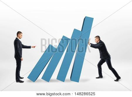 Rival businessman pushing the blocks of a graph that another businessman holding back from falling. Competition and rivalry. Financial market. Coworkers.