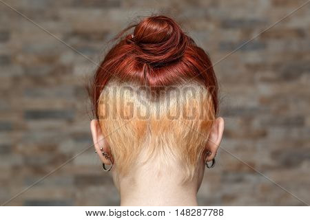 young model with colored topknot and hidden undercut bleached hair