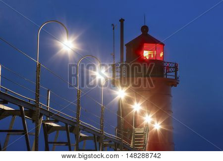 Lights shine during twilight at the red lighthouse on Lake Michigan at South Haven Michigan.