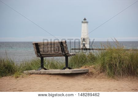 A park bench in dune grass on the Frankfort, Michigan beach with the lighthouse in the background.